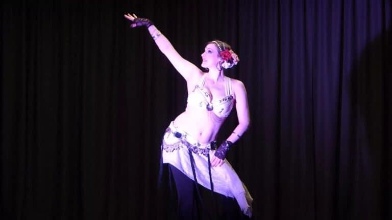 Danseuse sur scène devant un rideau sombre, elle est au centre de l'image le bras droit levé et le visage qui suit son bras