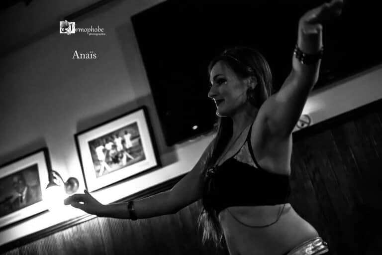 Photo en noir et blanc d'une danseuse souriante les bras à hauteur des épaules