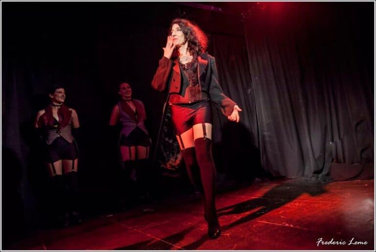 Trois danseuses sur scène dont une qui avance la main sur la bouche