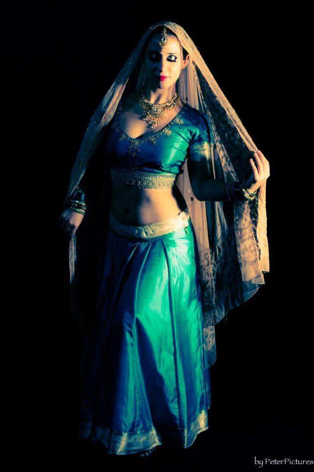 Photo de danseuse habillée en bleu avec un voile au sommet de sa tête qui retombe sur les épaules et le long de son corps
