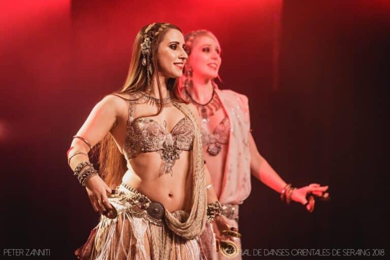 Deux danseuses sur scène dont une floue, l'arrière plan de la scène est rouge
