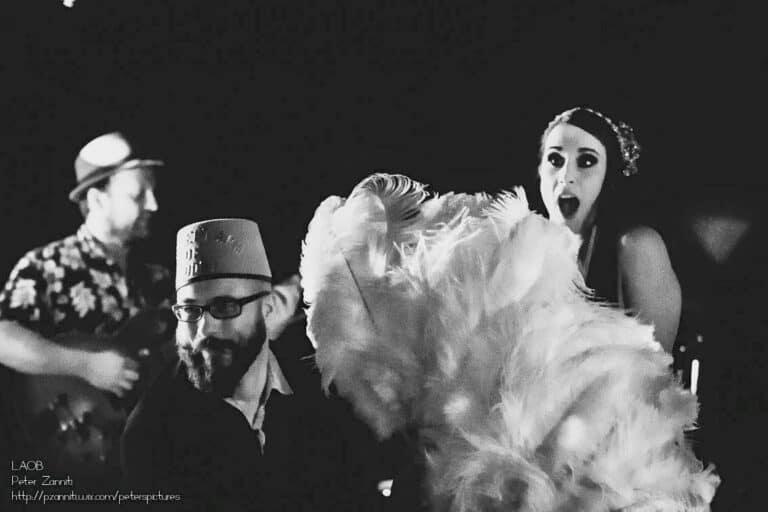 Danseuse sur scène avec un éventail en plumes et deux musicien dont un flou en arrière plan. Photo en noir et blanc