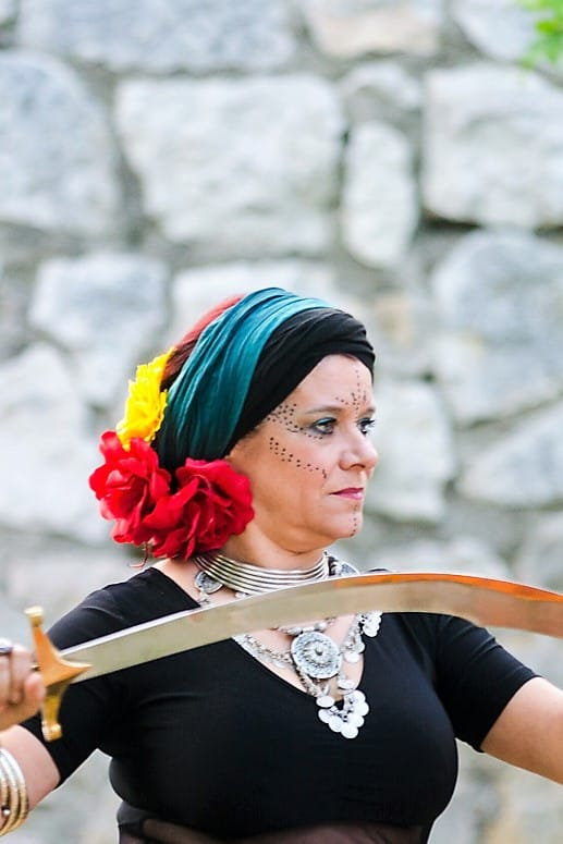 Danseuse avec un maquillage de scène, turban, flers et sabre