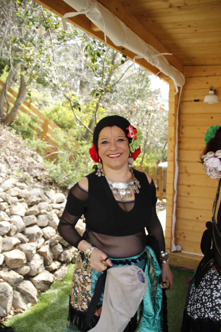 Danseuse souriante en tenue de danse avec maquillage, fleurs et turban sur la tête