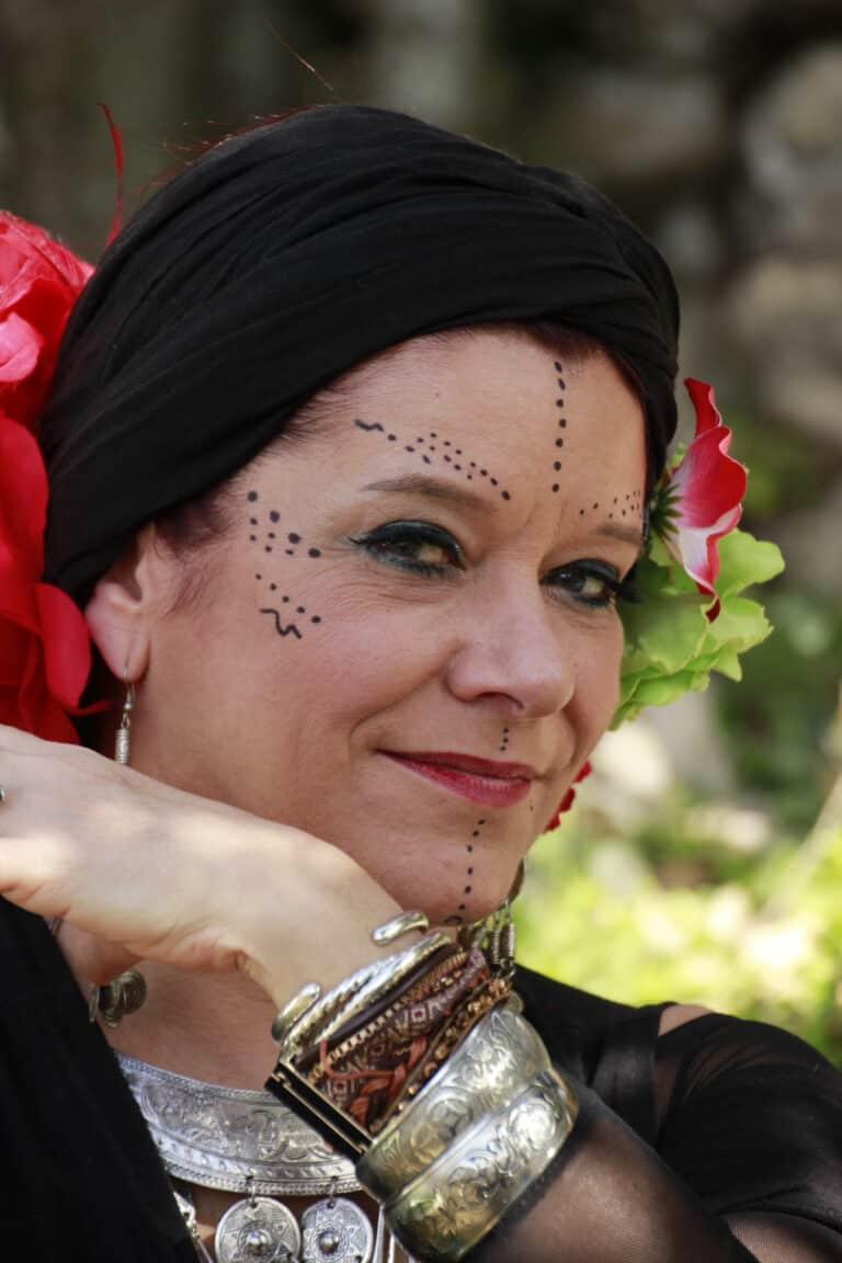 Danseuse prend la pose en souriant. Elle a un maquillage de scène, des bijoux, un turban sur la tête avec des fleurs