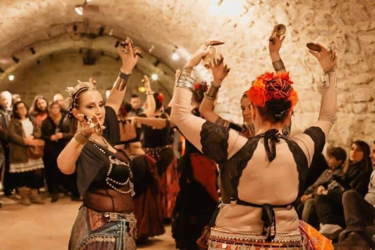 Trois danseuses en cercle entourées de public