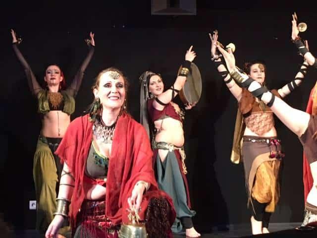 Danseuses sur scène dont celle du premier plan habillée en rouge qui tient une chaîne