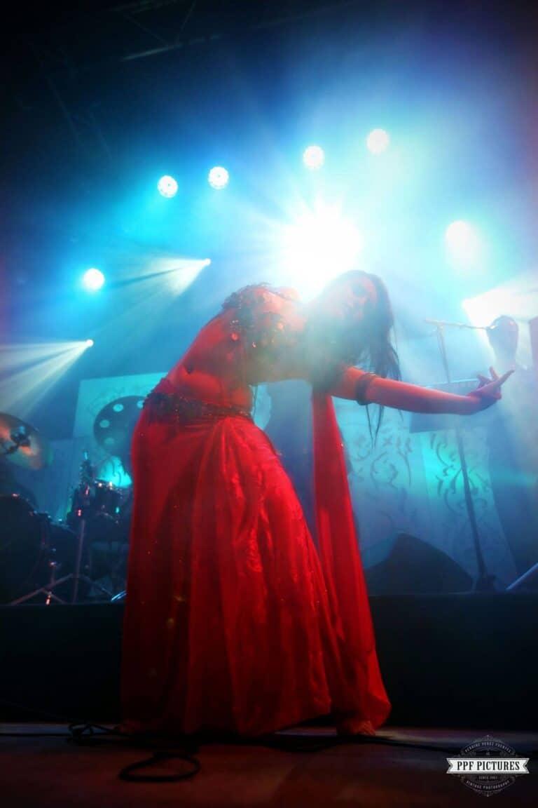 Danseuse en robe rouge sur scène avec des lumières bleues