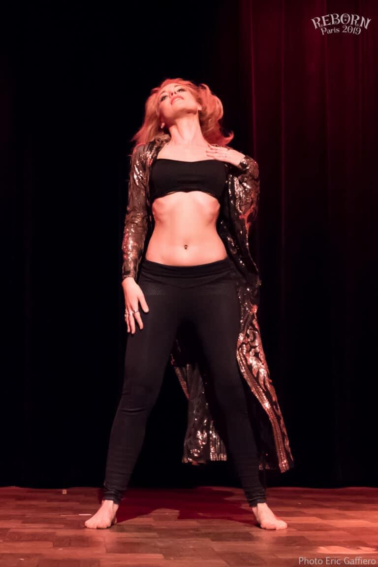 Danseuse debout sur scène avec un éclairage rouge