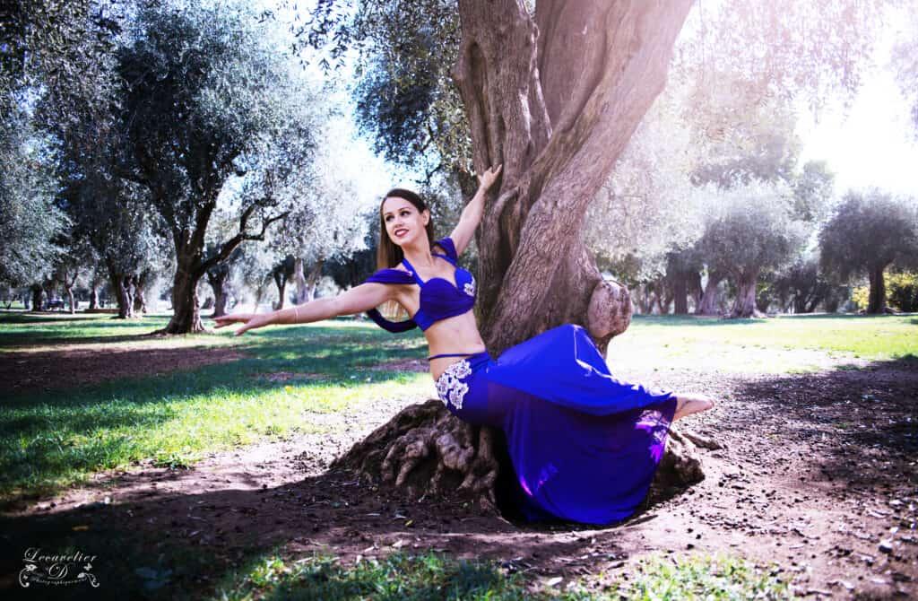 Danseuse orientale avec un robe bleue prends la pose sur un arbre