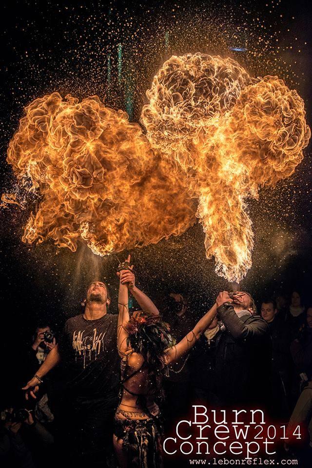 Danseuse aux mains de feu entourée par deux cracheurs de feu