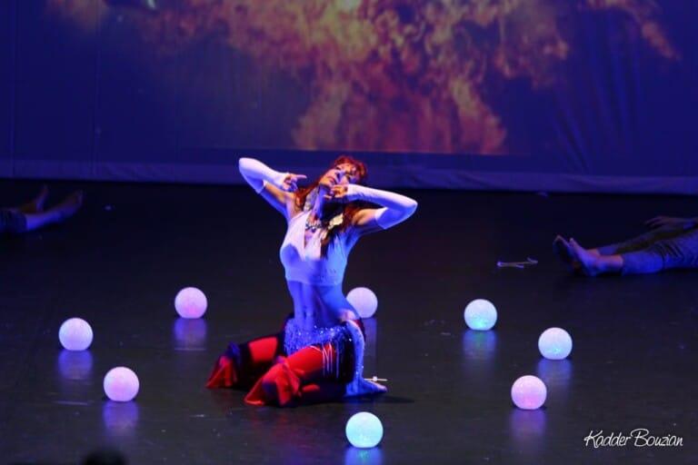 Danseuse à genoux sur scène entourée de boules lumineuses