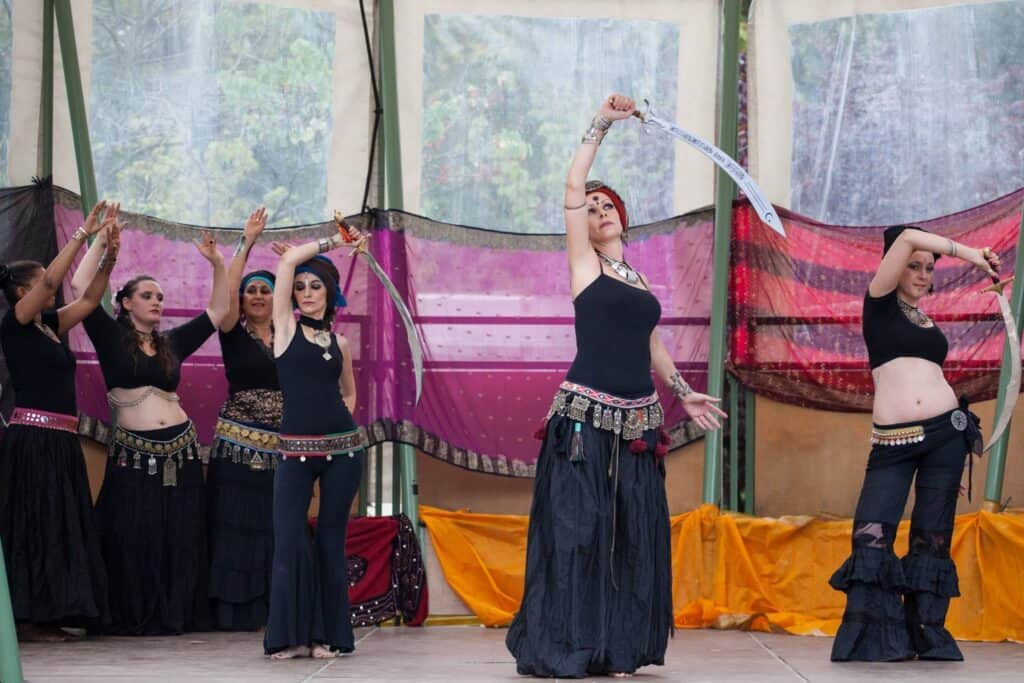 La tribu Parfum Tribal sur scène, dont trois danseuses au premier plan avec des sabres
