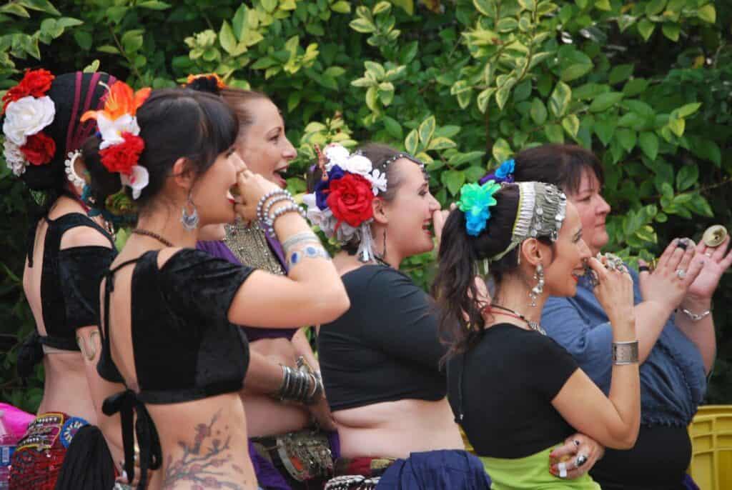 Six danseuses de la tribu Parfum tribal, de profil, qui semblent faire des youyous