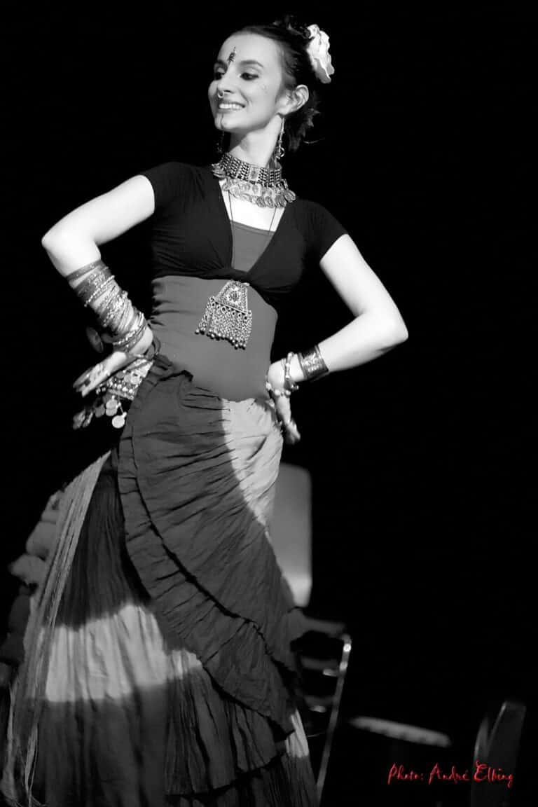 Photo noir et blanc de la danseuse souriante avec un bondi sur le front et une fleur dans les cheveux