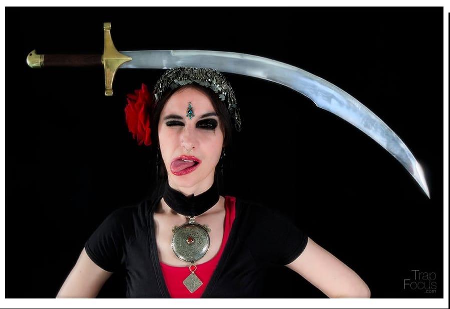 Danseuse qui tire la langue avec un sabre sur la tête