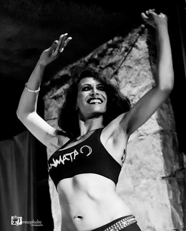 Photo danseuse souriante sur scène. Elle porte un débardeur et a les bras levés. La photo est en noir et blanc.