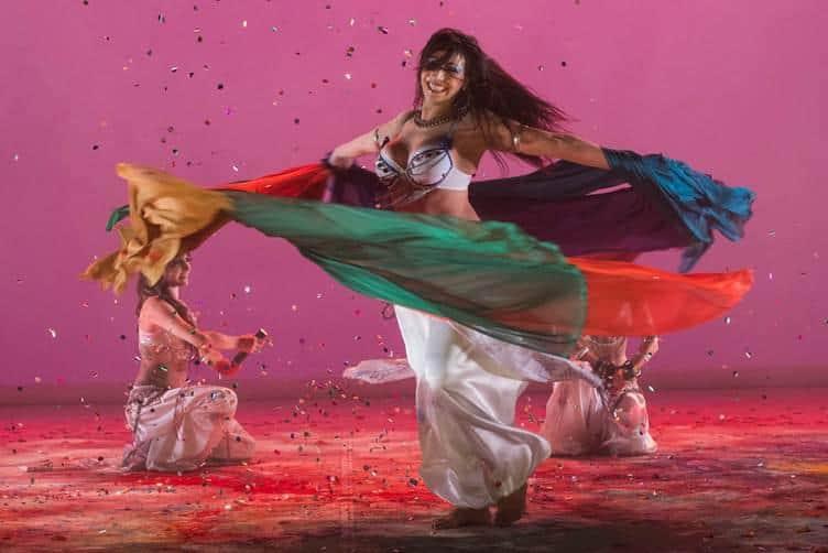 Danseuse qui tourne avec des voiles. Elle est souriante, les cheveux longs et il y a beaucoups de couleurs sur scène.