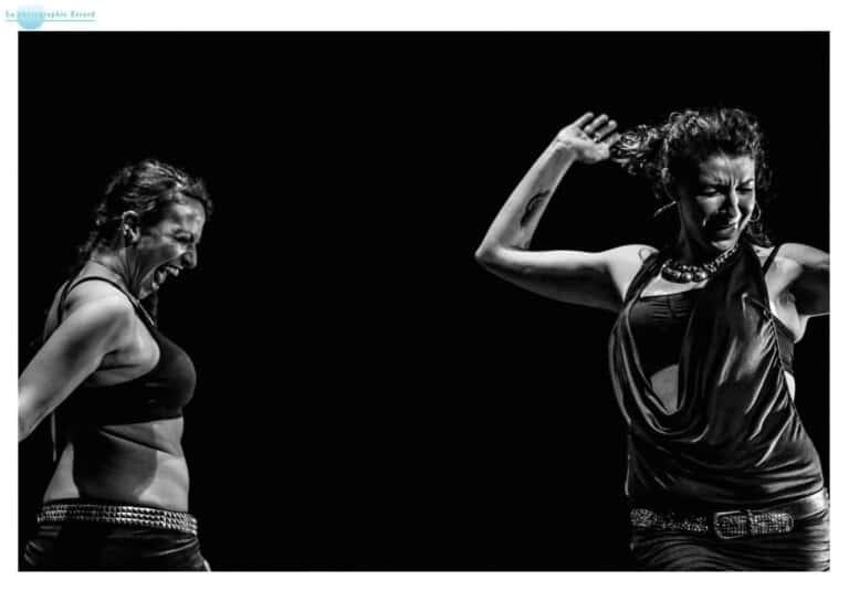 Deux danseuses sur scène, en noir et blanc, dont une qui semble crier et l'autre emportée par le souffle de ce cri qu'elle reçoit