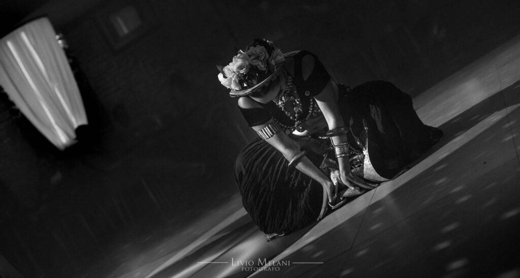 Danseuse sur scène accroupie et mains posées au sol. Photo en noir et blanc