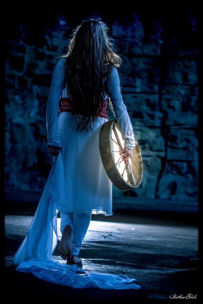 Danseuse en blanc de dos avec un tambour à la main droite et un linge à la main gauche