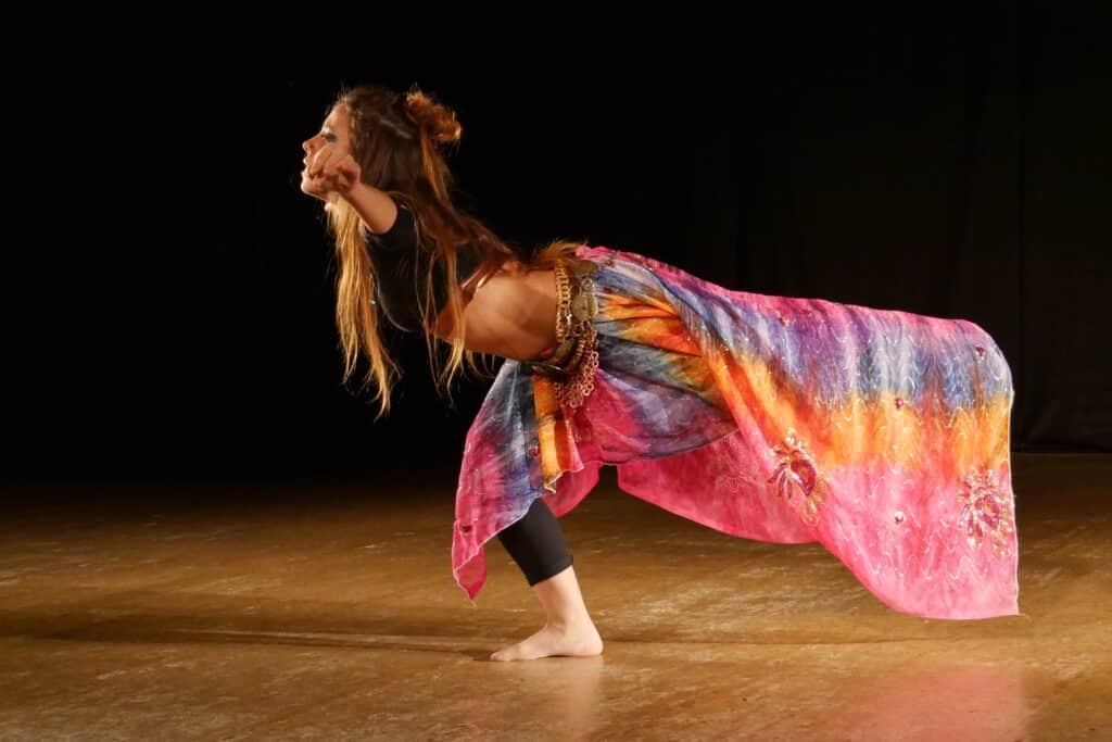 Freeze sur scène, danseuse sur une jambe, bras écartés