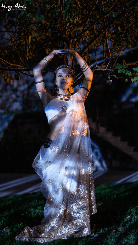 Danseuse qui prend la pose de nuit devant un arbre