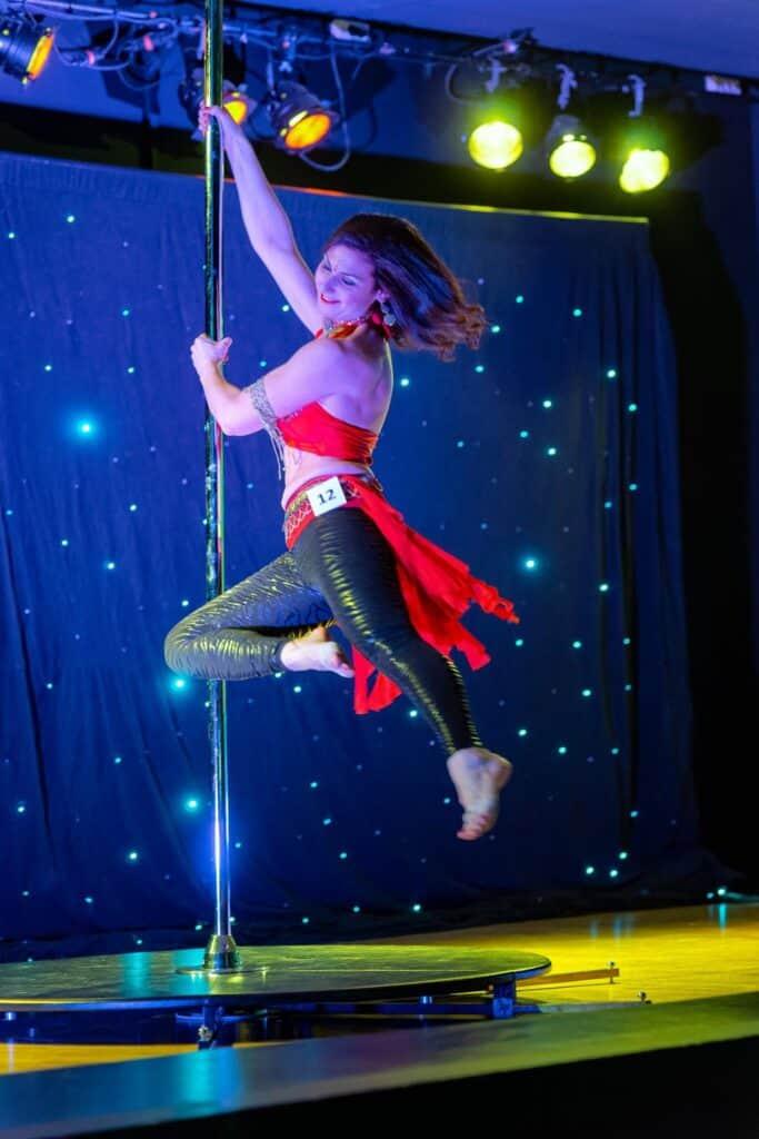 Kalyndra danseuse pole dance en plein mouvement exécute une figure sur la barre