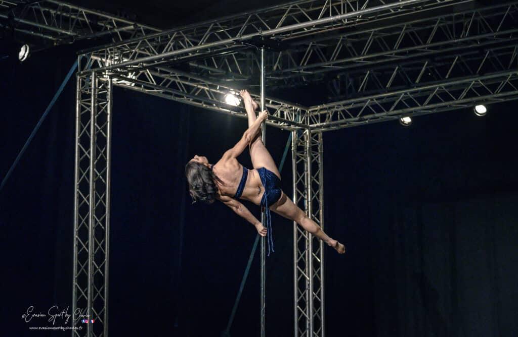 Kalyndra danseuse pole dance de dos en plein mouvement sur la barre